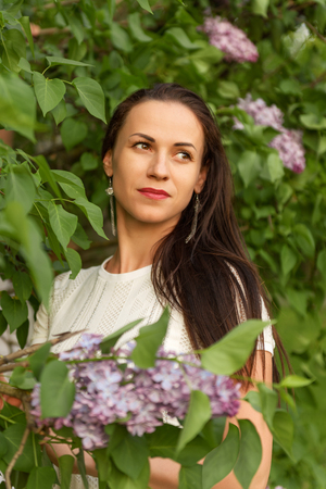 portrait of a young dreamy woman in a white vintage knitted dress in lilac bushes
