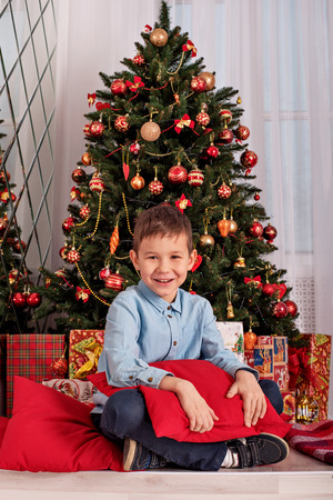 boy sitting near the Christmas tree hugging a cozy pillow on New Year's Eve Stock Photo