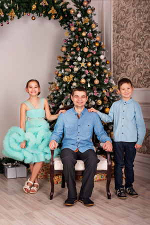 father with daughter and son in elegant clothes on Christmas eve near the New Year tree at home