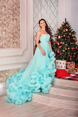 attractive elegant woman in a lush blue dress stands near the Christmas tree in a New Years decorated interior of the house 版權商用圖片