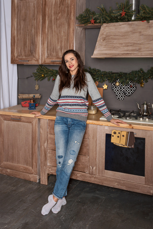 portrait of a young attractive brunette woman on a new-year decorated kitchen