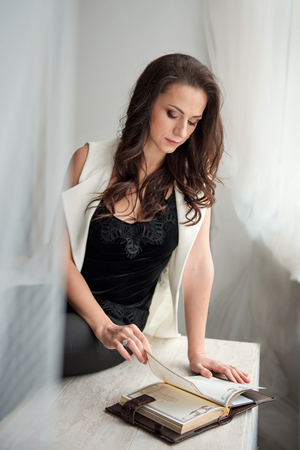 beautiful brunette woman sitting under a white fabric canopy and looking at a diary
