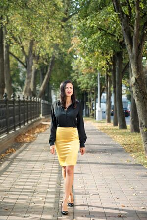 portrait of a young elegant business woman walking on the sidewalk among the trees in a shirt and skirt