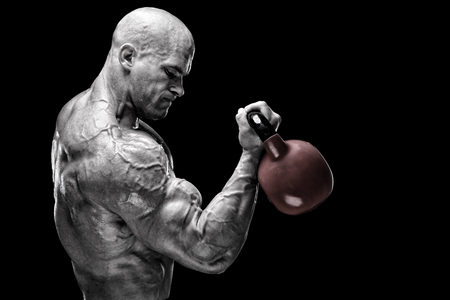 Bodybuilder exercising with kettlebells in front of black background