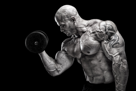 Bodybuilder exercising in front of black background