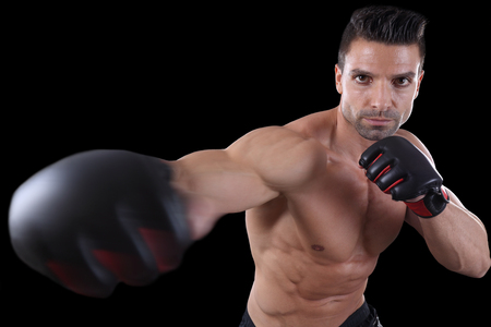 Muscular fighter punching in front of black background