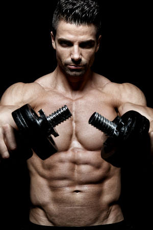 Muscular bodybuilder exercising in front of black background Stock Photo