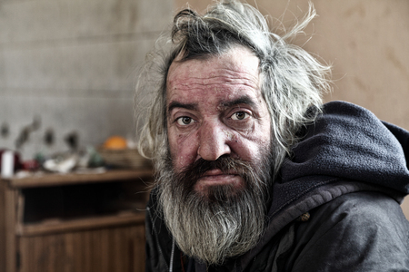 Poor homeless man sitting in abandoned house