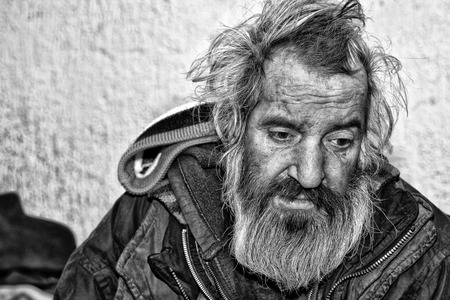 Homeless man sitting in abandoned house Stock Photo