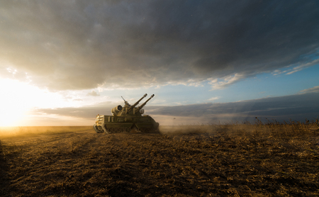 cold war: heavy tank in a field with two guns