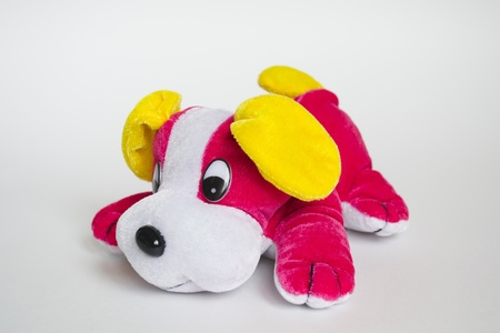 Pink lying toy dog with yellow ears on grey background