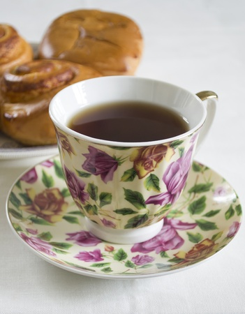 Cup of black tea with floral ornament on a saucer photo