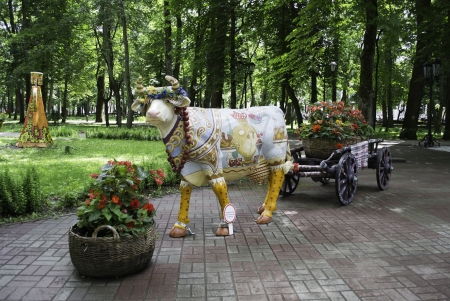 Decorated cow with cart filled a basket with flowers