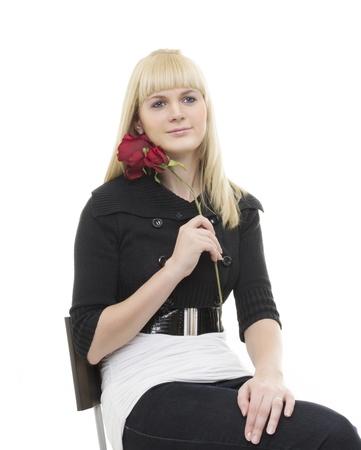 Mulher de sorriso que senta-se na cadeira com flor em sua m Banco de Imagens