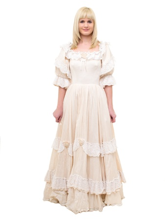 Beautiful Victorian Lady standing in white background. Beige Dress with flowers, Ruffles and Lace. Long fair straight Hair. Looking at the Camera.  Stock Photo