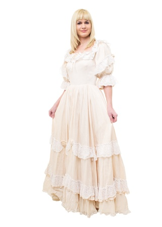 Beautiful Victorian Lady standing in sideway in white background. Beige Dress with flowers, Ruffles and Lace. Long fair straight Hair. Looking at the Camera.  photo