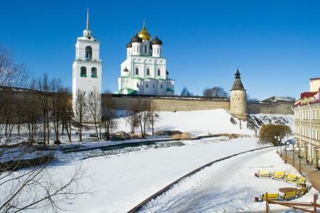 Harsh parede da antiga Pskov Kremlin (Krom), Trinity catedral ortodoxa, torre sineira e aterro no dia de inverno ensolarado, Pskov, R Banco de Imagens