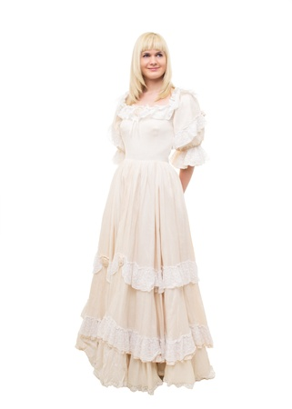 Beautiful Victorian Lady standing in sideway in white background. Beige Dress with flowers, Ruffles and Lace. Long fair straight Hair. Looking at the right up corner.