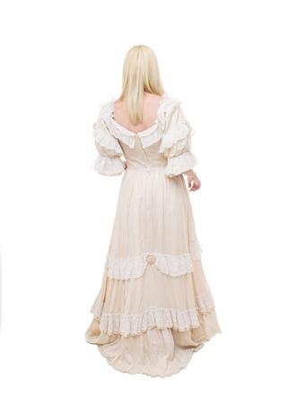 vestidos de epoca: Victorian Lady Bella est� caminando en el fondo blanco. Vista desde atr�s. Vestido de color beige con flores, volantes y encajes. Pelo largo recto justo.
