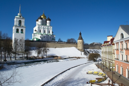Harsh wall of ancient Pskov Kremlin (Krom), Trinity orthodox cathedral, bell-tower and embankment at sunny winter day, Pskov, Russia Banco de Imagens
