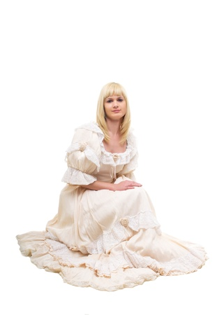 Beautiful Victorian Lady sitting in sideway in white background. Beige Dress with flowers, Ruffles and Lace. Long fair straight Hair. Looking at the Camera. photo