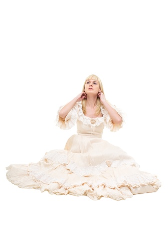 Beautiful Victorian Lady sitting in white background. Beige Dress with flowers, Ruffles and Lace. Long fair straight Hair. Spruce up.