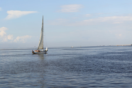 Beautiful yacht with white sails on the brightly light-blue sky and quiet bay
