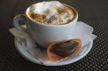Cup of cappuccino with cinnamon and chocolate lips Stock Photo