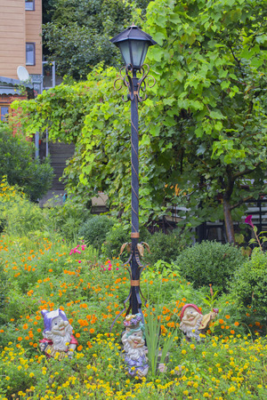Example of garden decoration: street lamp and figurines of dwarf in garden decor