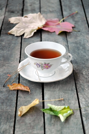 White vintage cup of tea on grey rustic wooden table, with autumn leaves