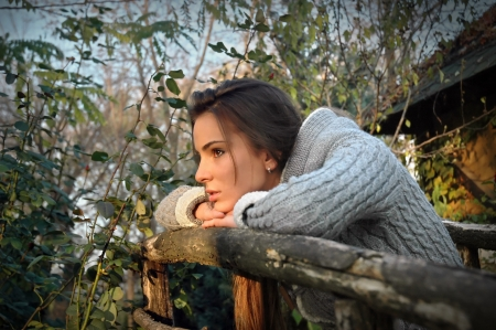 beautiful woman leaning chin on old wooden fence, thinking photo