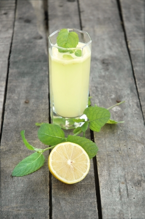 Glass of lemonade with mint and cut lemon on wooden table Stock Photo - 22606204
