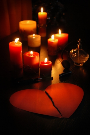 love letter in shape of broken heart with candles and romantic old perfume bottle