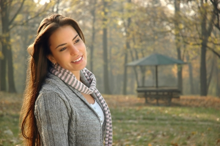 pensive young woman smiling and posing in autumn park   Copy space