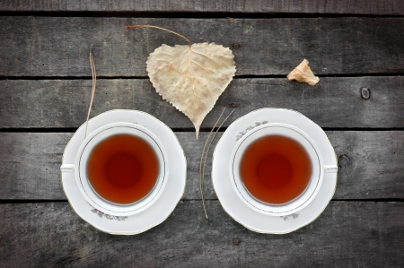 autumn  tea for two  in vintage white cups on a grey rustic wooden table, with autumn leaves and pine needles
