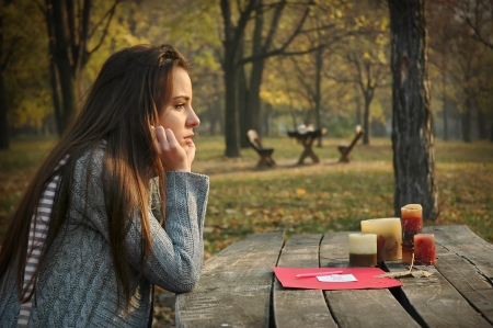 young woman sitting at old wooden table with paper and candles on it, in autumn park, pensive look Stock Photo - 22606221