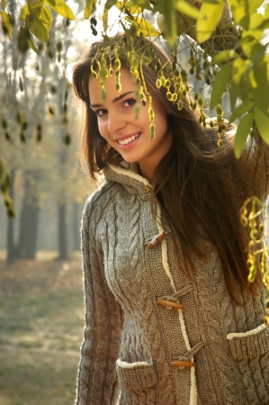 beautiful young woman peeking behind tree Stock Photo