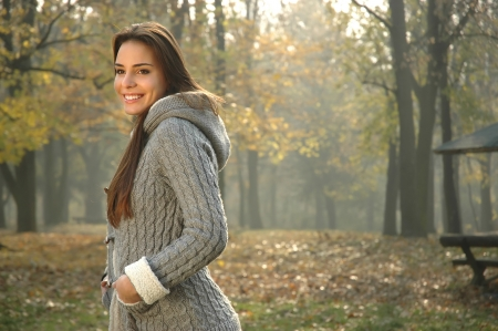 smiling woman in autumn park, dressed in gray sweater with hood, hands in pockets,   copy space  Stock Photo