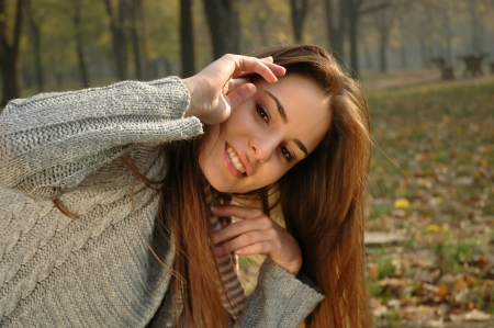 Smiling woman removing hair from her face in autumn park