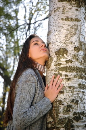 Beautiful woman leaned on a birch watching the sky