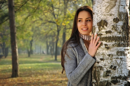 beautiful woman smiling, leaned on a birch tree Stock Photo