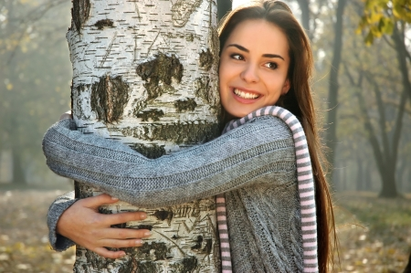 young beautiful woman smiling and hugging  a birch tree