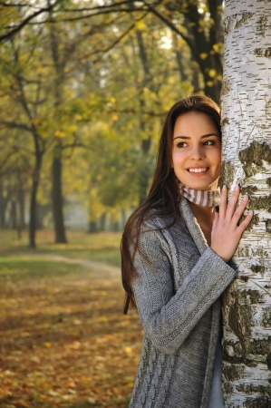 woman smiling, leaned on a birch tree Stock Photo
