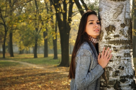 young pensive woman leaned on birch in autumn park Stock Photo