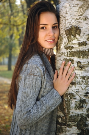 leaned: Young woman leaned on a birch, hugging tree, smiling