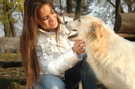beautiful young woman smiling and enjoying playing with white dog  who looks like smiling too