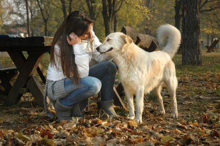 woman talking to a dog in autumn park