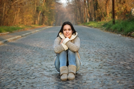 young woman sitting in the middle of a old road made of stone cubes  cobble