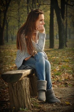 Pensive woman sitting on bench in autumn park, thinking  Noise added