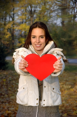 beautiful woman in white jacket holding paper in shape of heart  Paper heart is flat, convenient for text